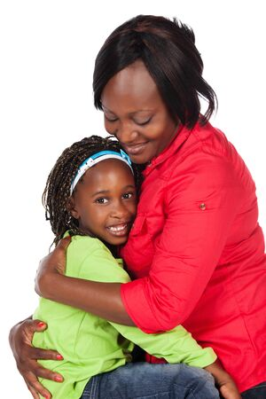 Adorable small african child with braids wearing a bright green shirt and blue jeans and her mother wearing a red shirt. The mom is holding and hugging the girl. photo