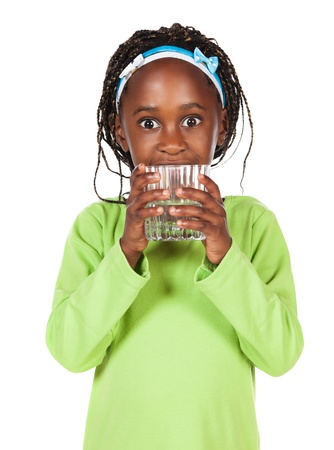 girl drinking water: Adorable small african child with braids wearing a bright green shirt. The girl is holding a clear glass of water. Stock Photo