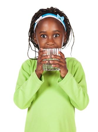 copa de agua: Pequeño niño africano adorable con las trenzas con una camisa de color verde brillante. La niña es la celebración de un vaso de agua clara. Foto de archivo