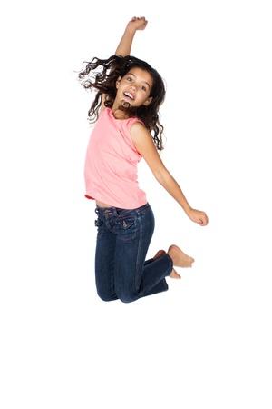 Vrij leuk Kaukasisch meisje draagt een roze bovenkant en blauwe jeans. Het meisje springt en lacht.
