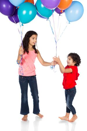 Pretty cute caucasian girl wearing a pink top and blue jeans and her sister wearing a red hooded top. They are holding a bunch of bright coloured helium balloons. photo