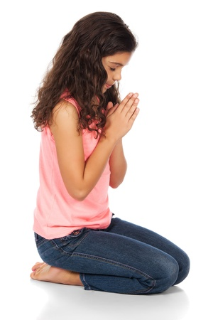 Pretty cute caucasian girl wearing a pink top and blue jeans. The girl is kneeling and praying. Stock Photo