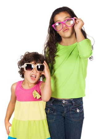 Pretty cute caucasian girl wearing a green long sleeve top and blue jeans and a smaller girl wearing a bright dress. Both are wearing sunglasses. photo