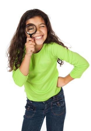 Schattig Kaukasisch meisje draagt een groene top met lange mouwen en een blauwe spijkerbroek. Ze speelt met een vergrootglas.