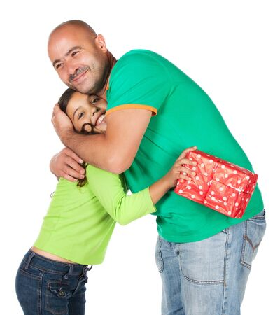 Pretty cute caucasian girl wearing a green long sleeve top and blue jeans and her father. He is giving her a gift in red wrapping paper. photo