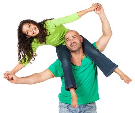 Pretty cute caucasian girl wearing a green long sleeve top and blue jeans is playing with her father. She is sitting on his shoulders. photo