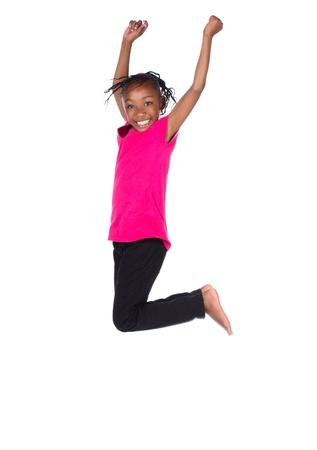 Schattig klein Afrikaans kind met vlechten draagt een fel groen shirt en zwarte skinny jeans. Het meisje springt en lacht. Stockfoto