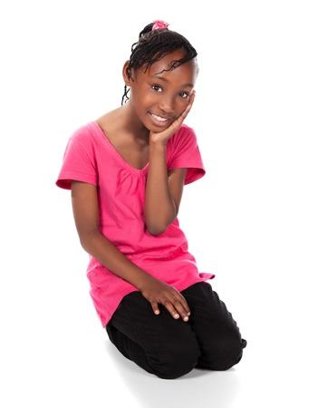 skinny jeans: Peque�o ni�o africano adorable con las trenzas con una camisa de color verde brillante y pantalones vaqueros flacos negros. La ni�a est� sentada y sonriendo a la c�mara.
