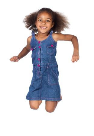 Aanbiddelijk Afrikaans kind met afro haar dragen een denim jurk. Het meisje springt en lacht.