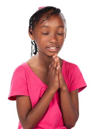 Adorable small african child with braids wearing a bright pink shirt. The girl is kneeling and praying. photo