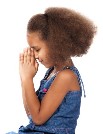 Adorable cute african child with afro hair wearing a denim dress. The girl is kneeling and praying. photo
