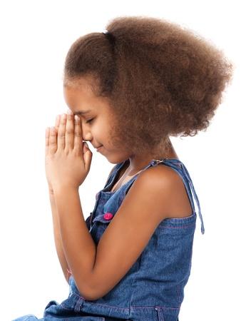 Schattige leuke Afrikaans kind met afro haar dragen van een denim jurk. Het meisje is geknield en bidden. Stockfoto