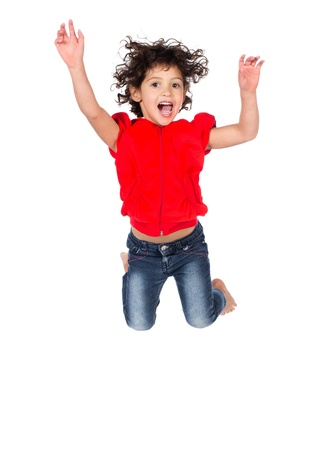 hooded top: Adorable small caucasian child with curly hair wearing a bright red hooded top and blue jeans. The girl is jumping and smiling. Stock Photo