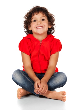 hooded top: Adorable small caucasian child with curly hair wearing a bright red hooded top and blue jeans. The girl is sitting and smiling at the camera. Stock Photo