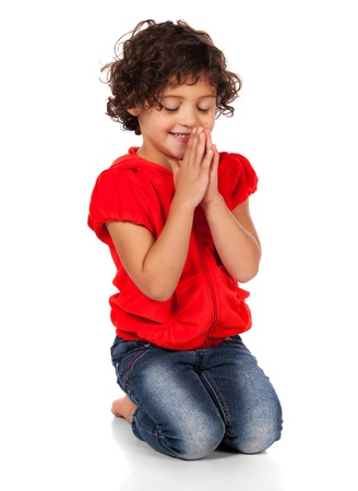 Adorable small caucasian child with curly hair wearing a bright red hooded top and blue jeans. The girl is kneeling and praying. photo