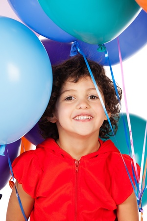 hooded top: Adorable small caucasian child with curly hair wearing a bright red hooded top. The girl is holding a bunch of bright coloured helium balloons.