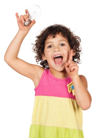 Adorable small caucasian child with curly hair wearing a pink blue and yellow dress. The girl is holding up a light bulb. photo