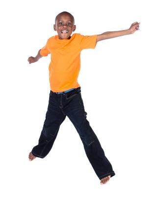 Leuke Afrikaanse jongen droeg een fel oranje t-shirt en een donkere denim jeans. De jongen springt en lacht.
