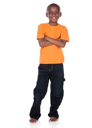 niños africanos: Muchacho africano lindo que lleva un color naranja brillante t-shirt y jeans oscuros. El niño está de pie y sonriendo a la cámara.