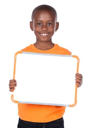 Leuke Afrikaanse jongen draagt een fel oranje t-shirt en donkere denim jeans. De jongen houdt een kleine witte bord en lacht naar de camera.