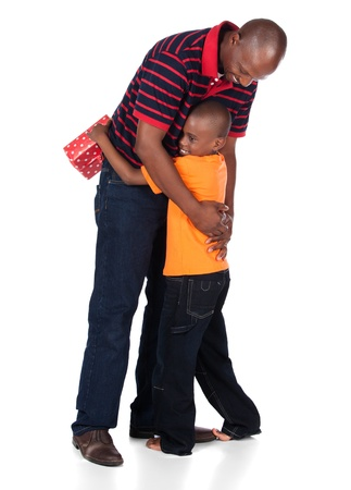 Cute african boy wearing a bright orange t-shirt and dark denim jeans is getting a gift from his father. photo
