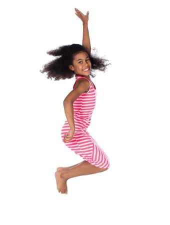 Aanbiddelijk Afrikaans kind met afro haar dragen een witte en roze gestreepte jurk. Het meisje springt en lacht.