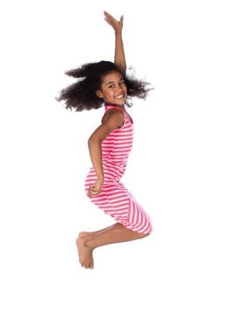 Adorable cute african child with afro hair wearing a white and pink striped dress. The girl is jumping and smiling.