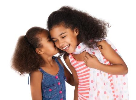 Twee schattige leuke Afrikaanse kinderen met afro haar. Men draagt een witte en roze gestreepte jurk en de andere een denim jurk. Ze fluisteren elkaar.