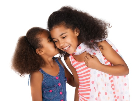 innocent girl: Two adorable cute african children with afro hair. One is wearing a white and pink striped dress and the other a denim dress. They are whispering to each other. Stock Photo