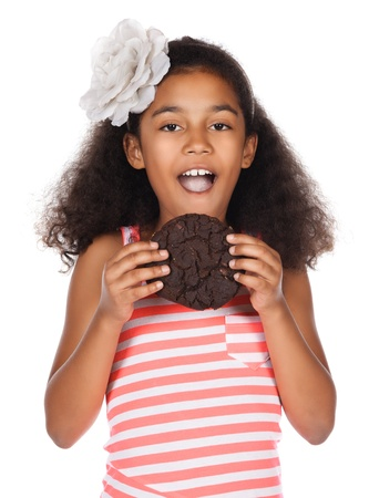 Adorable cute african child with afro hair wearing a white and pink striped dress. The girl is holding a big choc chip cookie. photo