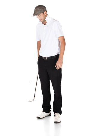Handsome young professional golf player wearing a white shirt and black pants. He is bouncing his golf ball on his club. photo
