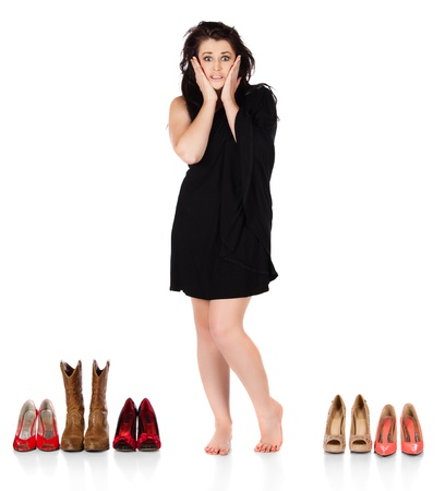 Cute young funky fashion girl wearing a black dress. She is looking at and deciding about many pairs of shoes. photo