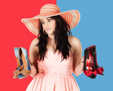 Cute young funky fashion girl wearing a pink coral dress and summer hat. She is holding and looking at high heel shoes. photo