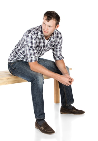 Handsome young attractive male fashion model wearing casual jeans and a checkered shirt. The man is sitting on a wooden bench and looking away from the camera. photo