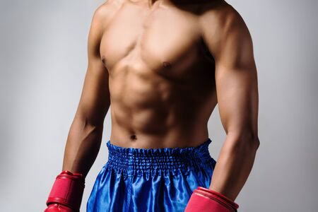 Young muscular athletic male boxer wearing blue boxing shorts and red boxing gloves. Fighter is on a grey background. photo