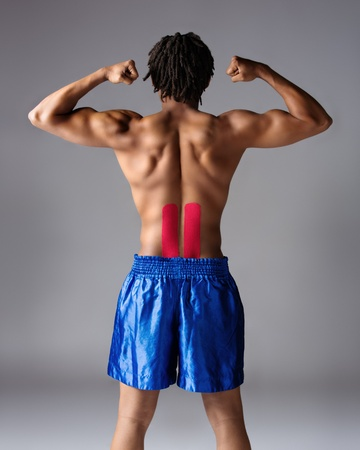 Young muscular athletic male boxer wearing blue boxing shorts. Fighter is on a grey background and has red strapping on his injured back. photo