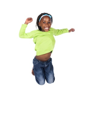 Adorable small african child with braids wearing a bright green shirt and blue jeans. The girl is jumping and smiling. photo