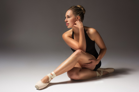 Beautiful young female classical ballet dancer wearing pointe shoes black leotard and ski-pants on a neutral grey studio background photo