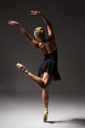Beautiful young female classical ballet dancer on pointe shoes wearing a black leotard and skirt on a neutral grey studio background photo