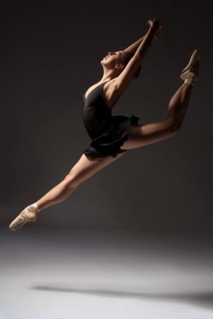 contemporary: Beautiful young female classical ballet dancer on pointe shoes wearing a black leotard and skirt on a neutral grey studio background