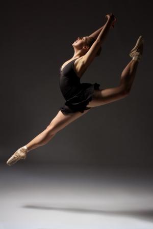 danza moderna: Hembra joven hermosa bailarina de ballet cl�sico en zapatillas de punta usando un leotardo negro y falda en un estudio de fondo gris neutro