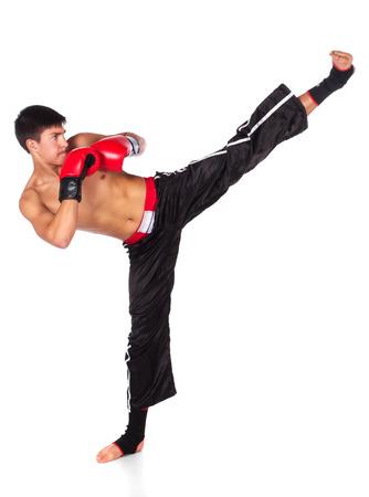 Giovane bel maschio caucasico kickboxer indossa i guantoni rossi e gli attrezzi kickboxing isolati su uno sfondo bianco