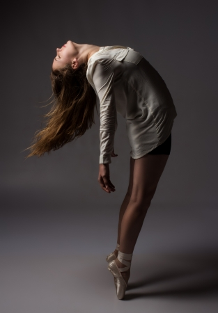 Beautiful slim young female modern jazz contemporary style ballet dancer on pointe shoes wearing a black leotard and white shirt on a neutral grey studio background photo