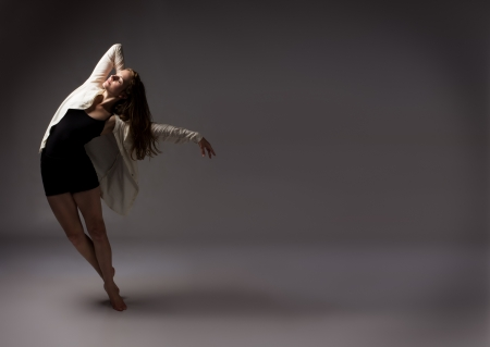 performing: Beautiful slim young female modern jazz contemporary style ballet dancer wearing a black leotard and white shirt on a neutral grey studio background