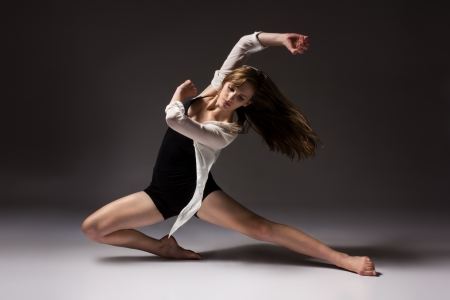 Beautiful slim young female modern jazz contemporary style ballet dancer wearing a black leotard and white shirt on a neutral grey studio background photo