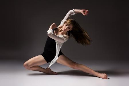 Mooie slanke jonge vrouw moderne jazz eigentijdse stijl ballet danser draagt een zwarte maillot en een wit overhemd op een neutrale grijze achtergrond studio
