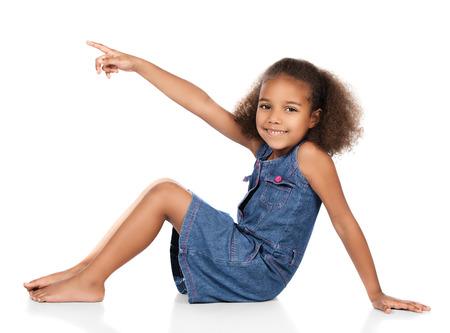 Schattig schattig Afrikaans kind met afro haar het dragen van een denim jurk. Het meisje zit en wijst weg van de camera.