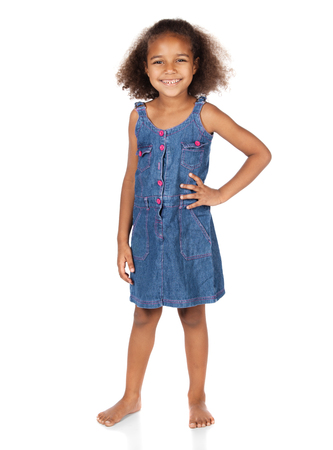 Adorable cute african child with afro hair wearing a denim dress. The girl is standing and smiling at the camera. Stock Photo