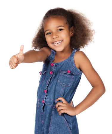 Aanbiddelijk Afrikaans kind met afro haar dragen een denim jurk. Het meisje toont een duim omhoog naar de camera. Stockfoto