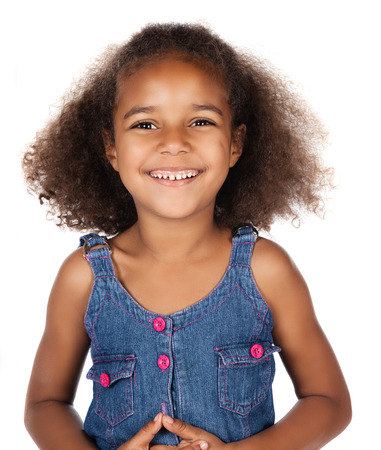 Adorable cute african child with afro hair wearing a denim dress. The girl is standing and smiling at the camera. Reklamní fotografie